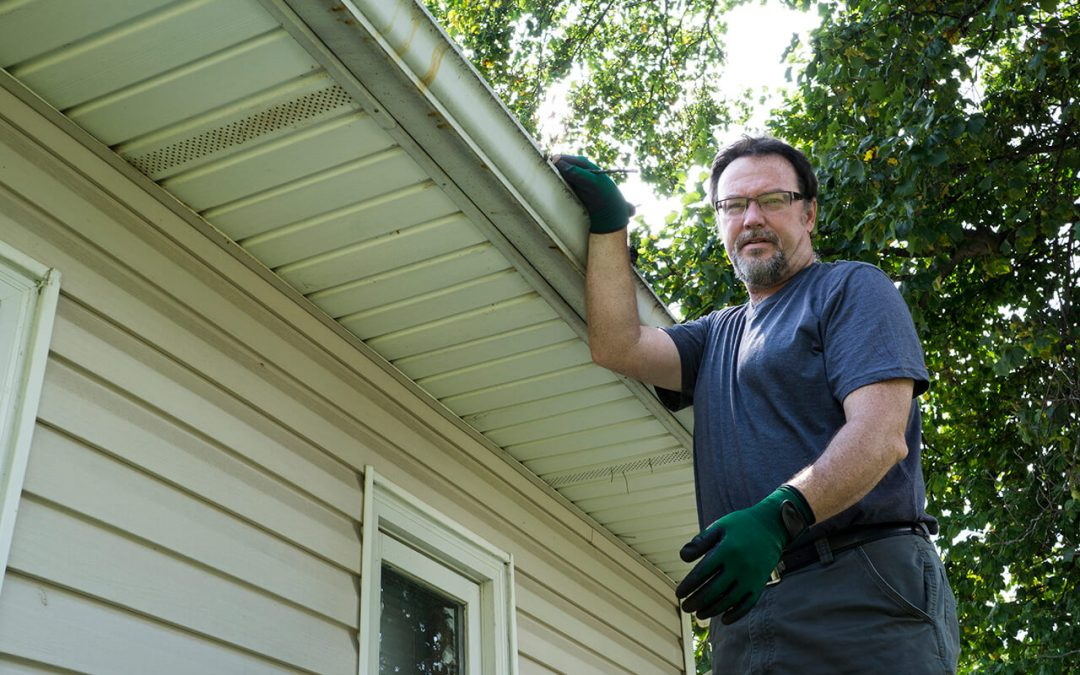 Man cleaning gutters to help reduce humidity in the home